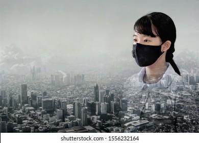 Portrait asiatische Kinder Mädchen tragen N95 Maske zum Schutz von PM 2,5 Staub und Luftverschmutzung. Portrait thailändischer StudentInnen mit Schutzmaske auf Smoking City Building mit schlechtem Wetter, pm2.5 Konzepthintergrund