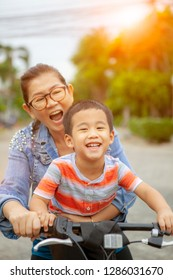 portrait of asian children riding bicycle with mother smiling face happiness emotion