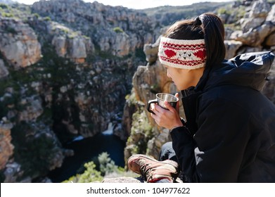 Portrait of an asian chinese backpacker smiling and drinking a mug of coffee while hiking and exploring on a tourist adventure in the wilderness mountains
