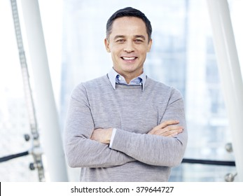 portrait of an asian (chinese) caucasian mixed-race business person in casual wear, arms crossed, smiling.
