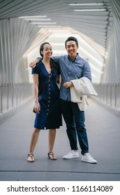 Portrait of an Asian Chinese couple on a date over the weekend. The man is young, handsome and well-dressed and the woman is wearing an elegant summer dress. They are smiling on a bridge.