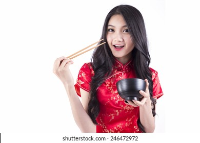Portrait of Asian Chinese female eating, using chopsticks in traditional dress red cheongsam isolated on white background
