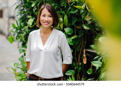 Portrait of an Asian Chinese female manager standing in the day. She is standing amidst plants in a garden or park in the day and smiling confidently.