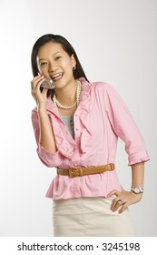 Portrait of Asian Chinese mid-adult female with hand on hip smiling and talking on cell phone.
