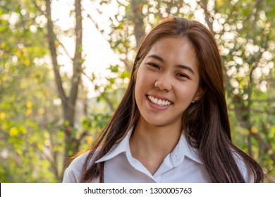 Portrait of asian college woman smiling in blur background witn sunlight