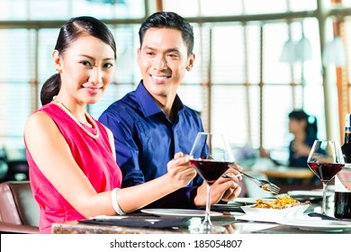 Portrait of asian couple eating and drinking red wine in restaurant
