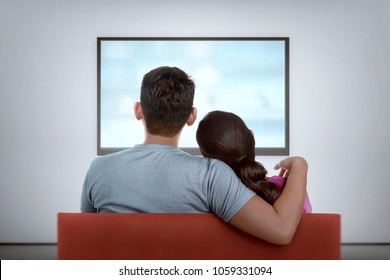 Portrait of asian couple on couch watching the television at home