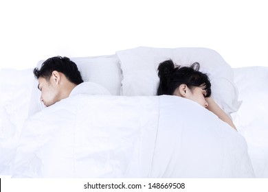 Portrait of asian couple sleeping back on back in bed. isolated on white background