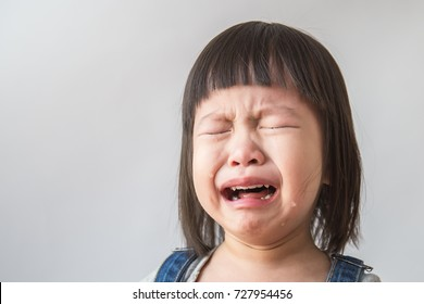 Portrait of asian crying little girl with little rolling tears weeping emotion, hurt in pain fit drops cheek. Young crying panic drama asian toddler in age of terrible two. Girl don't cry concept.