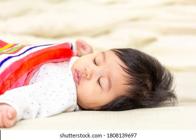 portrait asian cute baby in a blanket sleeping on the bed in room