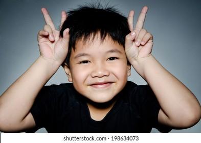 Portrait Of asian cute boy on gray background .