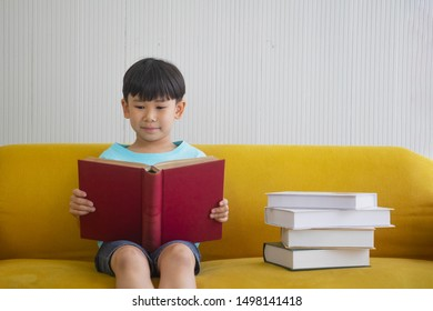 Portrait Asian cute boy.Child boy sitting with a books on Yellow sofa.Boy reading a book beside book row.lovely,nice, development.photo concept knowledge and  Kid portrait.