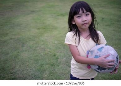 Portrait Asian cute little girl Holding a soccer ball