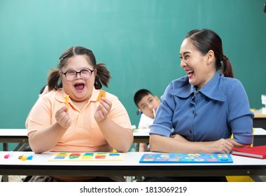 portrait asian disabled child or down syndrome child showing alphabet toy puzzle and woman teacher helping in classroom