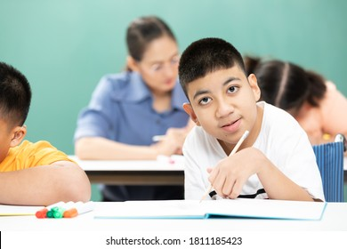portrait asian disabled kids or autism child learning looking and writing at desks in classroom