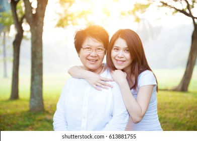 Portrait of Asian elderly mother and daughter, senior adult woman and grown child. Outdoors family at nature park with beautiful sun flare.