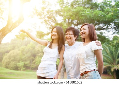 Portrait of Asian elderly mother and daughters pointing looking away, senior adult woman and grown child. Outdoors family at nature park with beautiful sun flare.