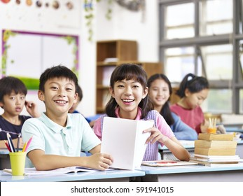 portrait of asian elementary school students in classroom looking at camera smiling.