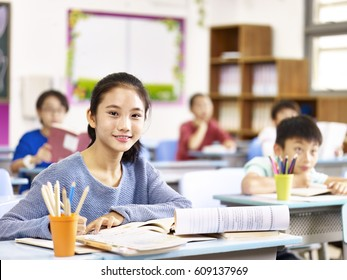 portrait of asian elementary schoolgirl sitting in classroom with classmates.