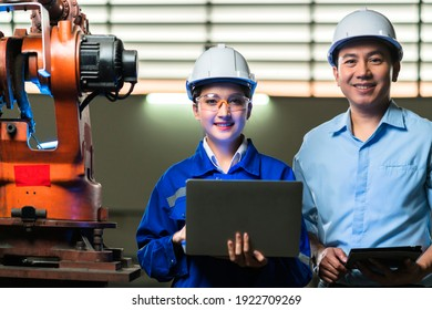 portrait of asian emgineer male female technician in safty uniform standing and turn around to look at camera and laugh smile with cheerful and confident in machinery factory workplace background