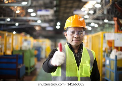 Portrait asian engineer showing thumb up in factory
