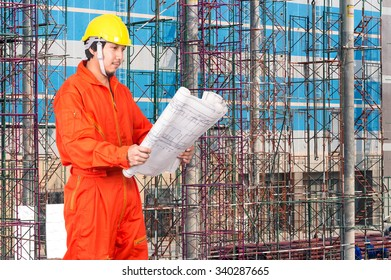 Portrait of Asian engineers looking at the blueprint on construction site workers, industrial construction concept