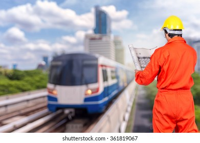 Portrait of Asian engineers looking at the blueprint on abstract Blurred photo of sky train, transportation industrial concept