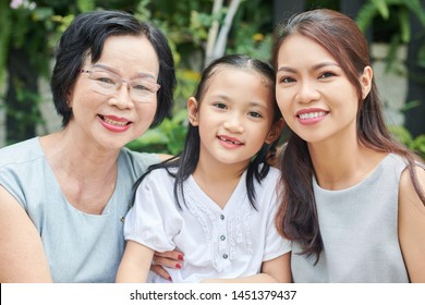 Portrait of Asian family generation embracing each other and smiling at camera outdoors