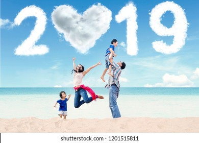 Portrait of Asian family having fun in the beach with clouds shaped heart and numbers 2019 in the sky