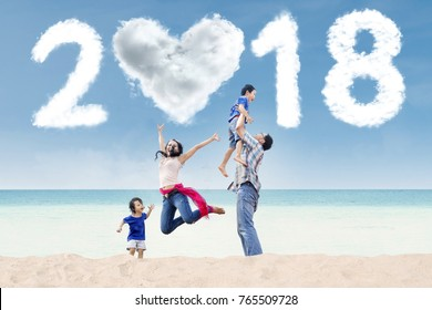 Portrait of Asian family having fun in the beach with clouds shaped heart and numbers 2018 in the sky