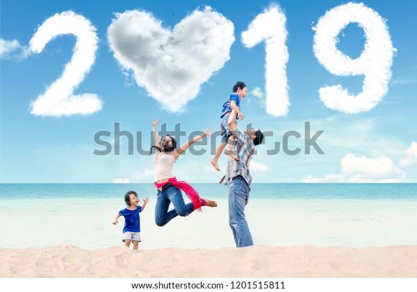Portrait der asiatischen Familie Spaß am Strand mit wolkenförmigen Herzen und Zahlen 2019 in den Himmel