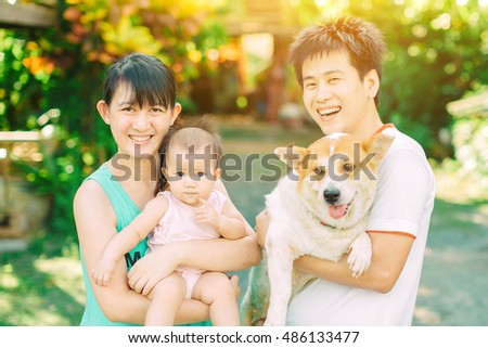 Portrait Of Asian Family Parents And Baby Who Smiling Together With Their Dog In
