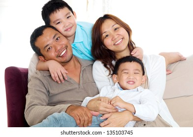 Portrait of asian family sitting on sofa