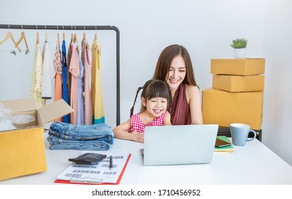 Portrait of asian family woman and girl packing box in the office business, family mother daughter moving house and small business, SME internet work from home business, single mom quarantine concept