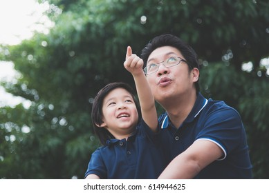 Portrait of Asian father and son looking up outdoors