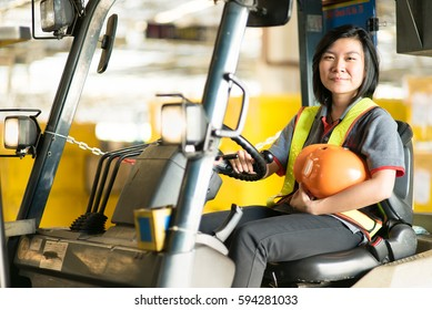 Portrait of Asian Female Fork Lift Truck Driver In Factory.