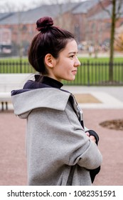 Portrait of asian female model with a laptop computer in her hands walking at the city park. She is dressed in gray coat and wears top knot bun hairstyle.