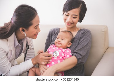 A portrait of an Asian female pediatrician examining a baby girl in the mother lap