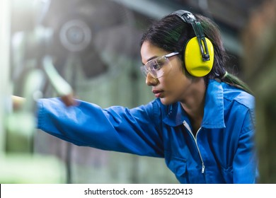 portrait asian female Professional engineering wearing uniform and safety goggles Quality control, maintenance, monitor screen checking process in factory, warehouse Workshop for factory operators