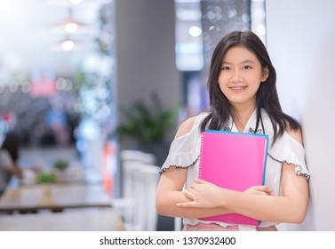 Portrait of Asian female studen  holding books.
