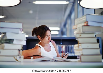 Portrait of asian female student sitting at the desk behind stack of books looking exhausted and tired to study, teenager sitting at the table with a huge pile of study books in university library