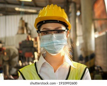 portrait asian female worker is wear protection mask face and safety helmet and wearing suit green reflective at factory. For working industrial due to covid pandemic crisis concept.