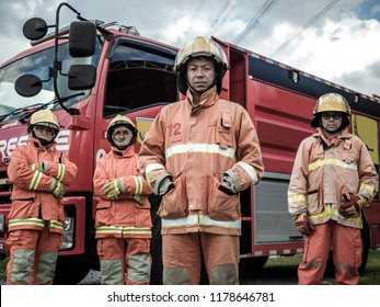 Portrait of asian firefighters standing together against truck at fire station