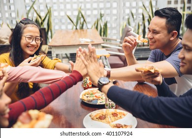 portrait of asian friend giving high five at cafe while having a lunch