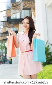 Portrait of an asian girl doing shopping outdoors