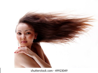 Portrait of the Asian girl with a flowing hair, a white background