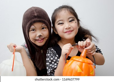 Portrait Asian girl with funny monster face holding pumpkin bucket and halloween costume