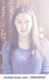 Portrait of an Asian girl in the light. In the background beautiful blurred lights garlands.