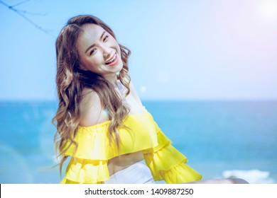 Portrait Asian girl long hair, bikini two-tone white and yellow, standing post happy posture by the sea, in Thailand South Asia, summer vacation, with concept of Charging happiness and relaxation