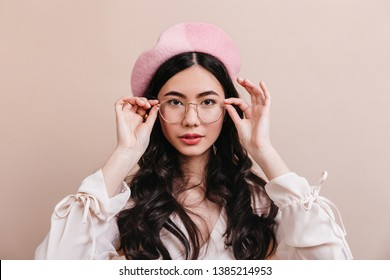 79a03c8a382fe Portrait of asian girl touching glasses. Front view of stylish korean model  in french beret